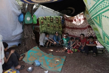 Displaced children sitting together in tent in camp in Idlib, Syria.