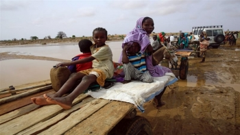 Internally displaced children and a woman sit on a car