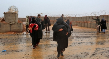 Mothers shielding their children from the harsh weather conditions in Rukban