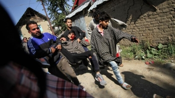 A group of Kashmiri men carrying a man injured during a gunfight in Kulgam