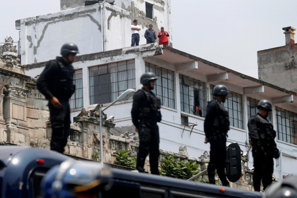 Mexican riot police keep watch over protesters from a teachers union as they take part in a march against President Enrique Peña Nieto's education reforms, in Mexico City on June 3.