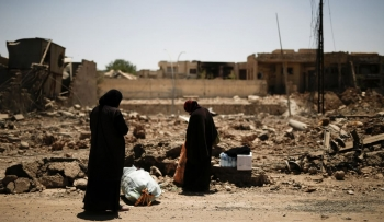 wo displaced Iraqi women stop to arrange their belongings as they flee from Mosul, Iraq