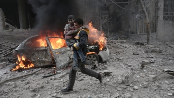 A Syrian paramedic carries a child injured in a bombing raid