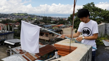 A young resident in Marawi displays a white flag on the rooftop of a house
