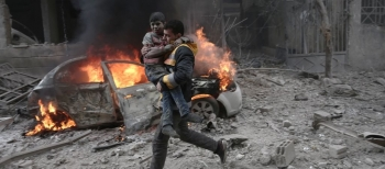 A Syrian paramedic carries an injured child