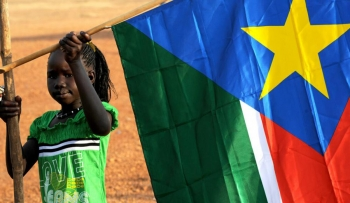 A child holding a South Sudanese flag