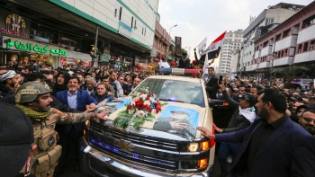 Mourners surround a vehicle carrying the coffins of Iranian Maj