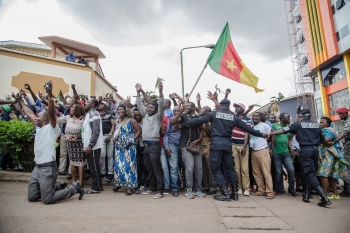 Cameroonians raising their national flag