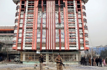 Afghan security forces in front of a building damaged by the explosion in Kabul, Afghanistan