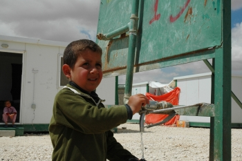A Syrian refugee child uses a water kiosk in Za'atari camp, Jordan