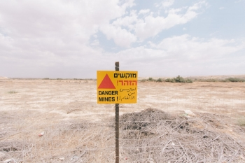 Sign warning of mines in front of a filed