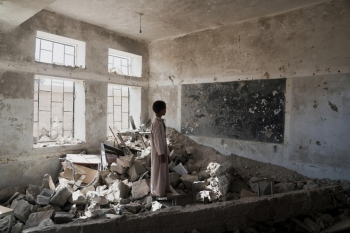 Student standing in the ruins of one of his former classrooms in Yemen