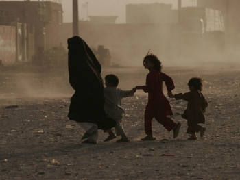 A woman and her children run across a dusty street in Herat Afghanistan