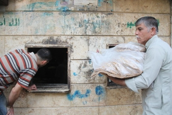 Two men are in front of a building in Aleppo, collecting daily bread relief