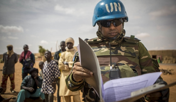 Peacekeeper of the UN Mission in Mali (MINUSMA) handling policy and guidance materials