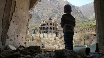 Yemeni child observing a war-torn city