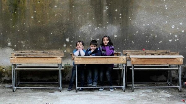 Syrian children in old schoolroom destroyed by bullets