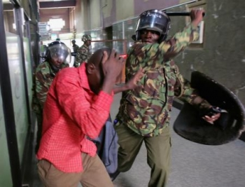 Policemen beat a protester inside a building during clashes in Nairobi, Kenya May 16, 2016.