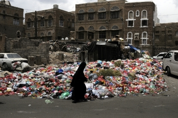 A woman walking next to rubbish heaps on the streets of Sana'a
