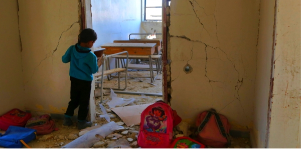 A Syrian child looks into a damaged school classroom in the city of Utaya, near Damascus