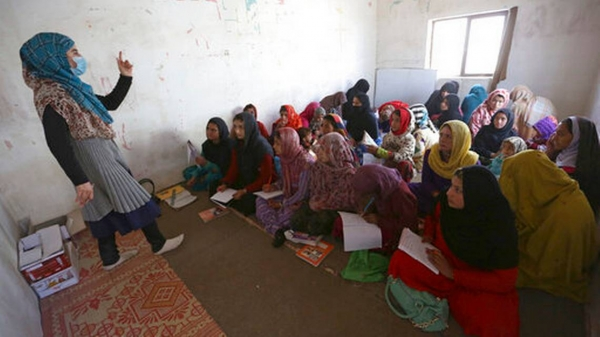 Afghan internally displaced school girls and women study at a class near their temporary homes on the outskirts of Kabul