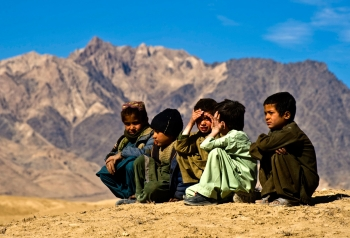 Afghan refugee children sitting on the top of a hill