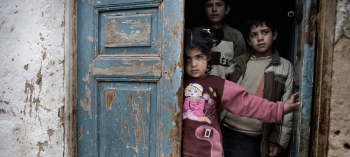 Syrian children in the doorway of a house.
