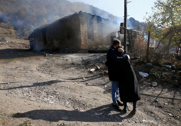 Residents hugging each other in front of a burning house in Kalbajar