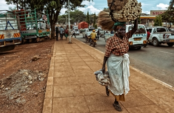 A woman carrying goods in a village in the Democratic Republic of Congo