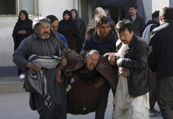 A distraught man is carried from the scene of the explosions in Kabul, Afghanistan.