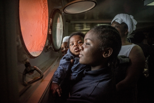 """Search and Rescue"" - A young African woman holding her baby tries to catch sight of European shores through the porthole."