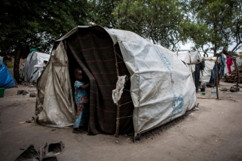 Child standing outside a tent in displacement site nearby Bunia (Kasenyi)