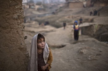 An Afghan girl stands by the doorway of her family's house in a poor neighborhood on the outskirts of Islamabad, Pakistan.