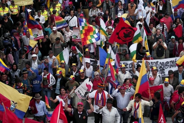 Protesters carry flags and banners while marching in Quito, Ecuador on August 12, 2015.