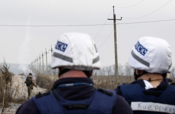 OSCE observers stand behind an officer launching signal rockets near Bohdanivka, in Donetsk region, 2019