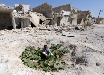 A Syrian man collects vegetables from a vegetable patch amongst the ruins of Baedeen, Aleppo, 2014