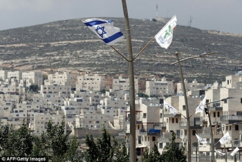 An Israeli flag flies high in front of a Jewish settlement in the area of Jerusalem
