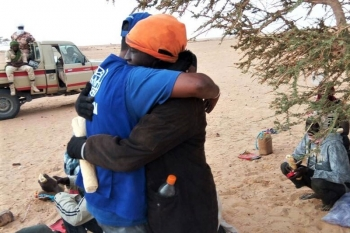 A migrant rescued after being abandoned by the driver hugs a IOM officer.