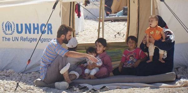 A displaced Syrian family rests at one of the UNHCR refugee camps