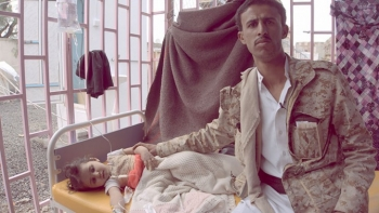 A young girl with cholera sits with her father in Yemen