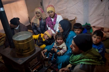 A Syrian refugee family gathered around a stove inside their shelter in Lebanon's Bekaa Valley.