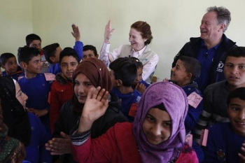 UNICEF and World Food Programme officials interact with children at a school in southern Idlib in Syria in March