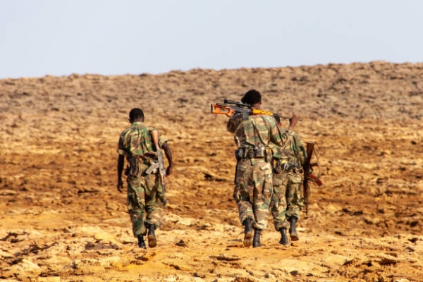 Three Ethiopian soldiers walking in the desert