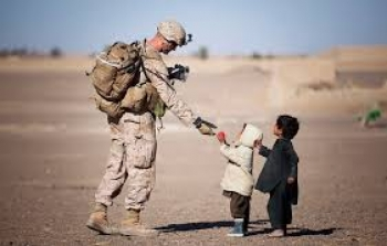 US Marine hands a toy to a child during a patrol mission in Afghanistan