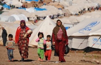 Two women walk alongside their children in a Syrian refugee camp