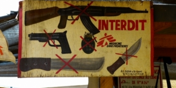 "A sign in front of a MSF Centre saying ""No arms allowed"""