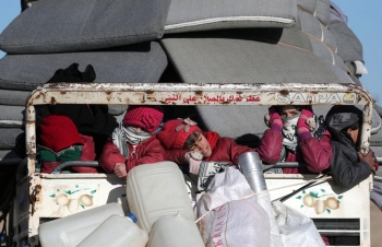 Syrian children fleeing Idlib ride on the back of a truck in Azaz, Syria, 24 January 2020.