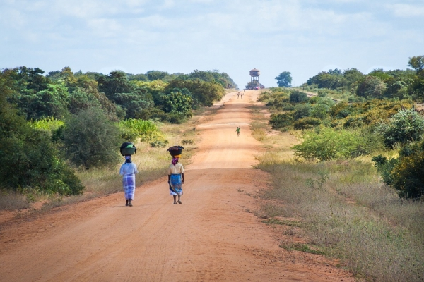 African women walking on a sand road in Mapai, Mozambique