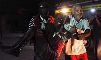 An injured man is carried from the scene of the attack in the centre of Mogadishu.
