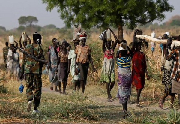 Women carrying their belongings in northern South Sudan are passed by a soldier